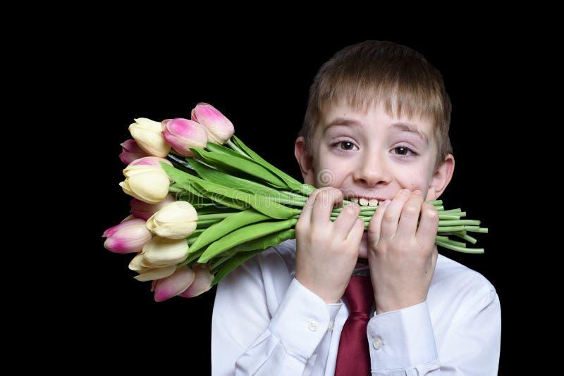 Αγόρι στο πουκάμισο και δεσμός που κρατά μια ανθοδέσμη των τουλιπών στα δόντια Απομονώστε στο μαύρο υπόβαθρο στοκ φωτογραφία