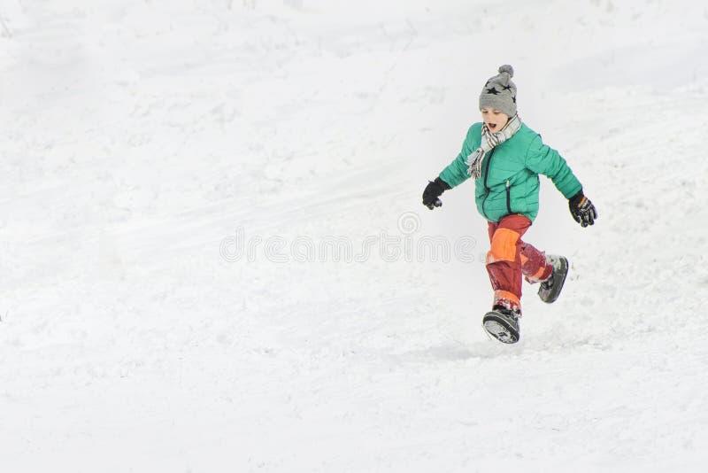 Αγόρι στο πράσινο σακάκι και κόκκινα τρεξίματα εσωρούχων μέσω του χιονιού ο μπλε παγετός σκοτεινής μέρας κλάδων βρίσκεται χειμώνα στοκ φωτογραφία με δικαίωμα ελεύθερης χρήσης