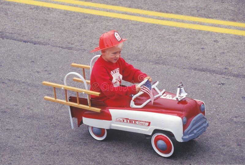 Αγόρι στο πυροσβεστικό όχημα παιχνιδιών στην παρέλαση στις 4 Ιουλίου, Cayucos, Καλιφόρνια στοκ εικόνα