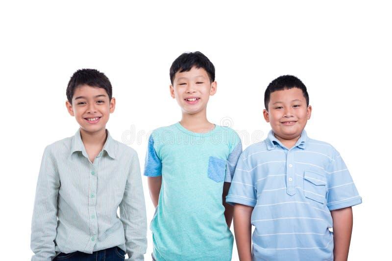 Αγόρι τριών σχολείων που στέκεται πέρα από το λευκό στοκ φωτογραφία