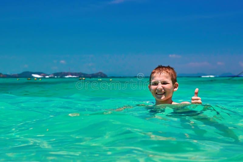 Αγόρι 10 χρονών που λούζει στην τυρκουάζ τροπική θάλασσα νερού Παιδί που χαμογελά παρουσιάζοντας αντίχειρα στοκ εικόνα