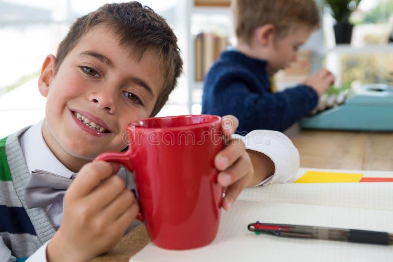 Αγόρι ως κούπα καφέ εκμετάλλευσης ανώτατων στελεχών επιχείρησης στην αρχή στοκ εικόνες με δικαίωμα ελεύθερης χρήσης