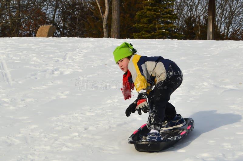 Αγόρι Snowboarding σε ένα έλκηθρο το χειμώνα στοκ εικόνες