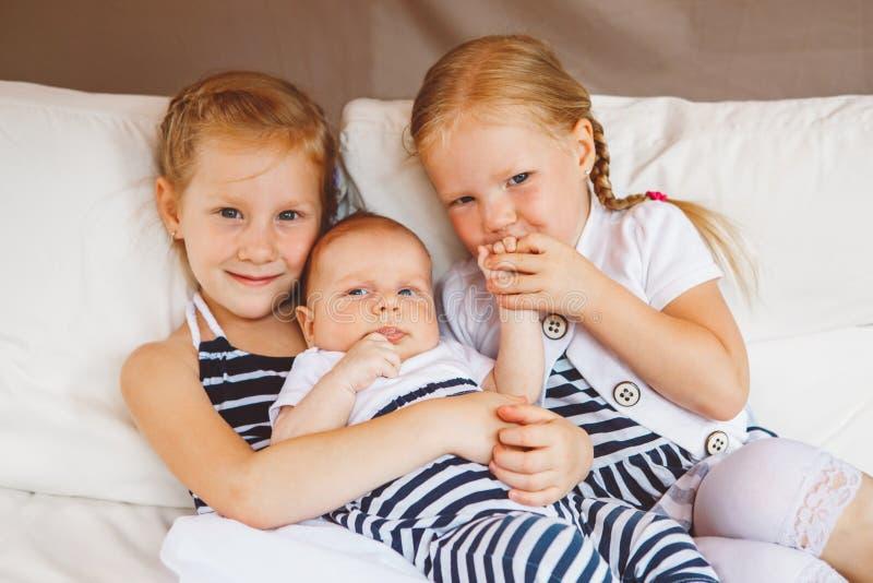 Αδελφές που κρατούν το φίλημα λίγου μωρού στοκ φωτογραφία με δικαίωμα ελεύθερης χρήσης
