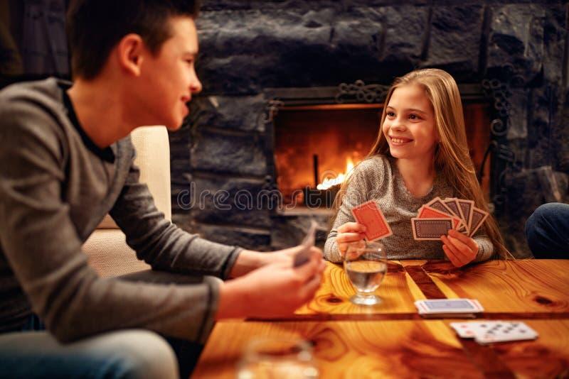 Αδελφός και αδελφή που έχουν τη διασκέδαση και που παίζουν τις κάρτες στο σπίτι στοκ φωτογραφίες
