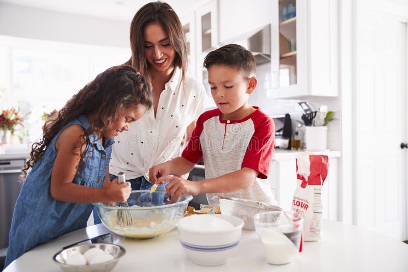 Αδελφός και αδελφή που κάνουν το μίγμα κέικ μαζί στον πίνακα κουζινών με το mum τους, μέση επάνω στοκ φωτογραφίες