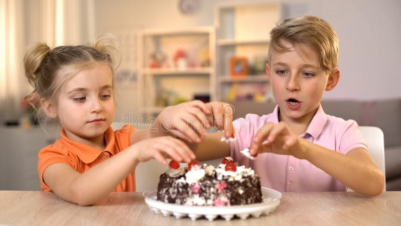 Αδελφός και αδελφή που παίρνουν τα κεράσια από την κορυφή του εύγευστου κέικ κρέμας, εορτασμός στοκ εικόνες με δικαίωμα ελεύθερης χρήσης