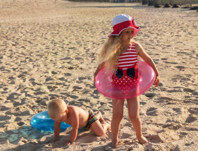 Αδελφός και αδελφή στους κύκλους για το παιχνίδι κολύμβησης στην ηλιόλουστη παραλία άμμου στοκ εικόνα με δικαίωμα ελεύθερης χρήσης