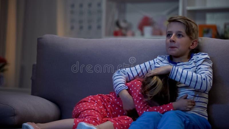 Αδελφός που αγκαλιάζει τη φοβησμένη αδελφή προσέχοντας τη νύχτα ταινιών φρίκης μαζί, οικογένεια στοκ φωτογραφία