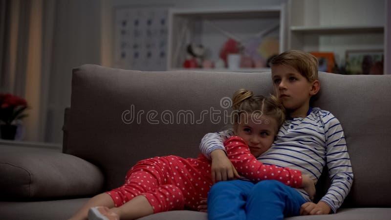 Αδελφός που αγκαλιάζει το κορίτσι, που προσέχει τη ταινία τρόμου, που προστατεύει την αδελφή από τα τέρατα στοκ εικόνες με δικαίωμα ελεύθερης χρήσης