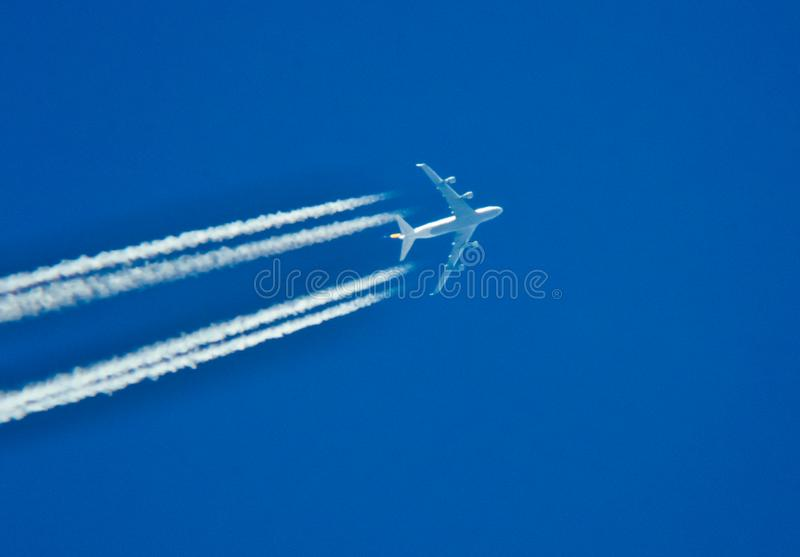 Αεριωθούμενο αεροπλάνο με τα ίχνη στο μπλε ουρανό στοκ εικόνα με δικαίωμα ελεύθερης χρήσης