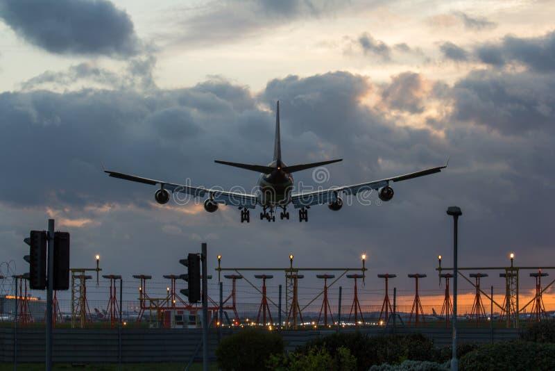 Αεριωθούμενο αεροπλάνο που προσγειώνεται στο ηλιοβασίλεμα στοκ εικόνα
