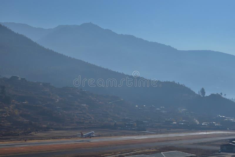 Αερολιμένας Paro στα βουνά - Μπουτάν τοπίο βουνών με το χωριό και το μίνι αερολιμένα στο διάδρομο ένα αεροπλάνο προσπαθεί να απογ στοκ εικόνα