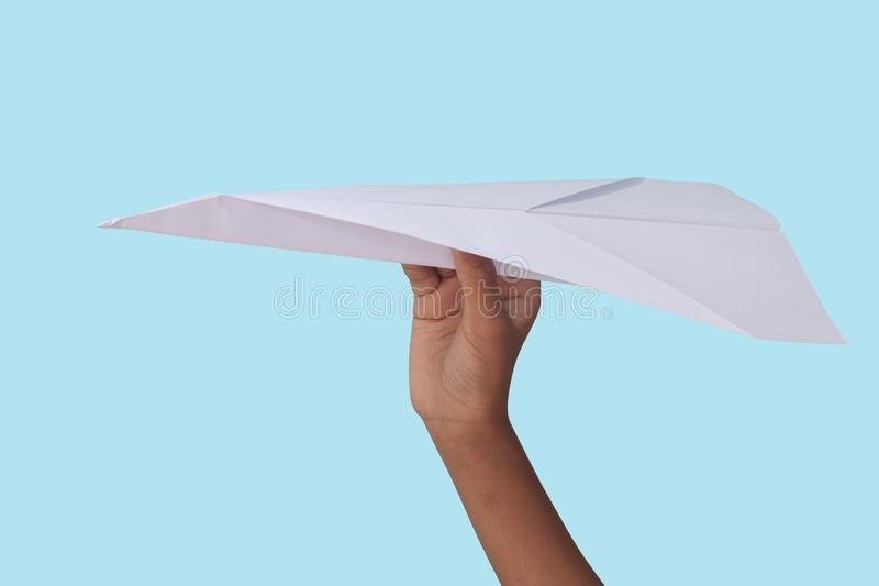 Αεροπλάνο εγγράφου πτυχών εκμετάλλευσης χεριών που απομονώνεται στο μπλε υπόβαθρο στοκ εικόνα με δικαίωμα ελεύθερης χρήσης