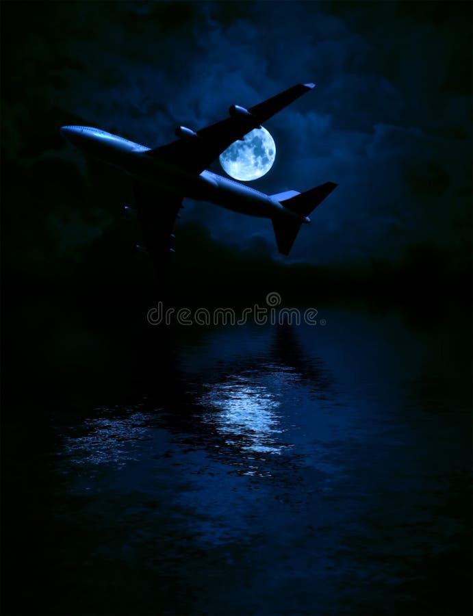 Αεροπλάνο και το φεγγάρι πέρα από τη θάλασσα στοκ φωτογραφία