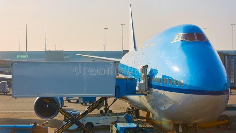 Αεροπλάνο κοντά στο τερματικό σε ένα πιλοτήριο αερολιμένων στοκ εικόνα με δικαίωμα ελεύθερης χρήσης