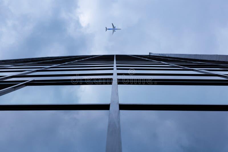Αεροπλάνο που πετά επάνω από το σύγχρονο κτίριο γραφείων γυαλιού αρχιτεκτονικής στοκ εικόνα