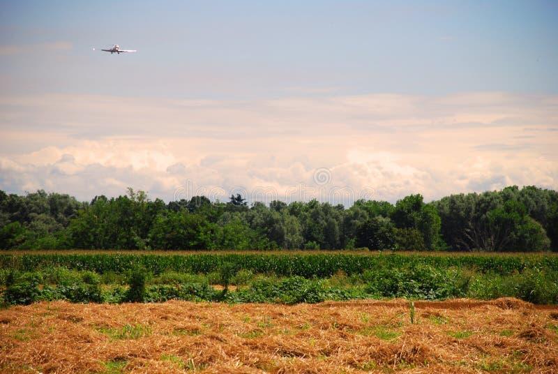 Αεροπλάνο που πετά πέρα από το πεδίο στοκ εικόνα με δικαίωμα ελεύθερης χρήσης