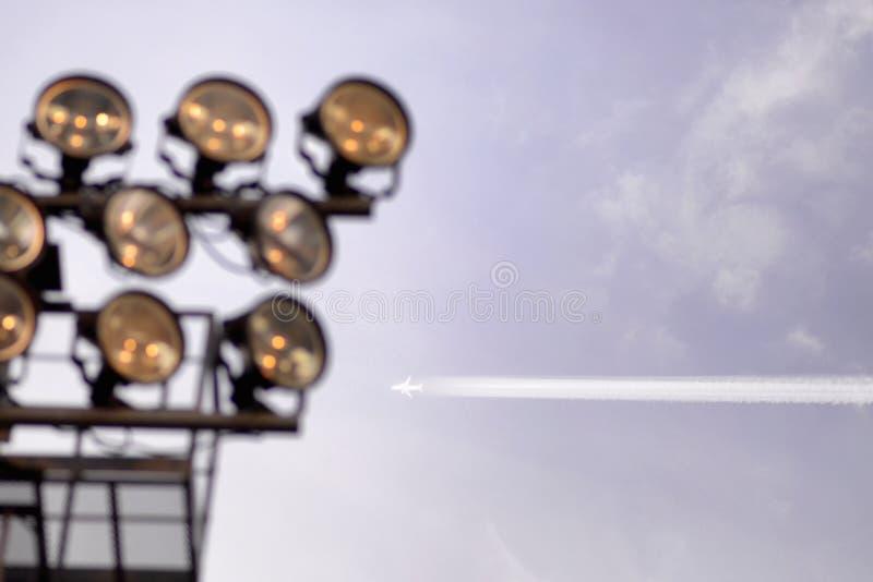 Αεροπλάνο που πετά στο μπλε ουρανό μεταξύ των σύννεφων και του φωτός του ήλιου Ενάντια στο σκηνικό του stadium' επίκεντρα του στοκ φωτογραφία