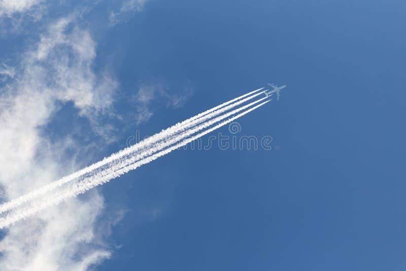 Αεροπλάνο στο νεφελώδη ουρανό με ένα αντίστροφο ίχνος στοκ εικόνα με δικαίωμα ελεύθερης χρήσης