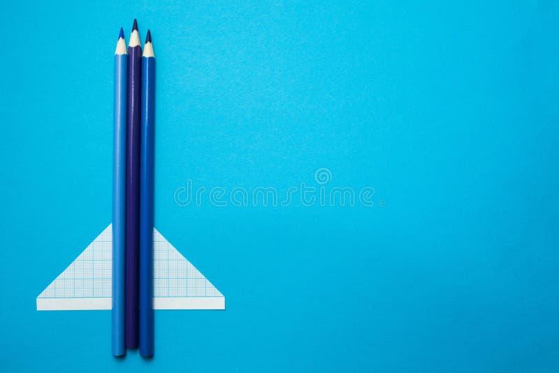 Αεροπλάνο φιαγμένο από μολύβια και έγγραφο για ένα μπλε υπόβαθρο r στοκ εικόνες
