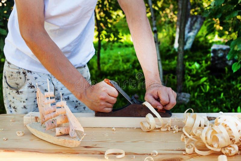 Αεροπλάνο εργασιών ατόμων ξυλουργών με το φραγμό των ξύλινων τσιπ στοκ εικόνα