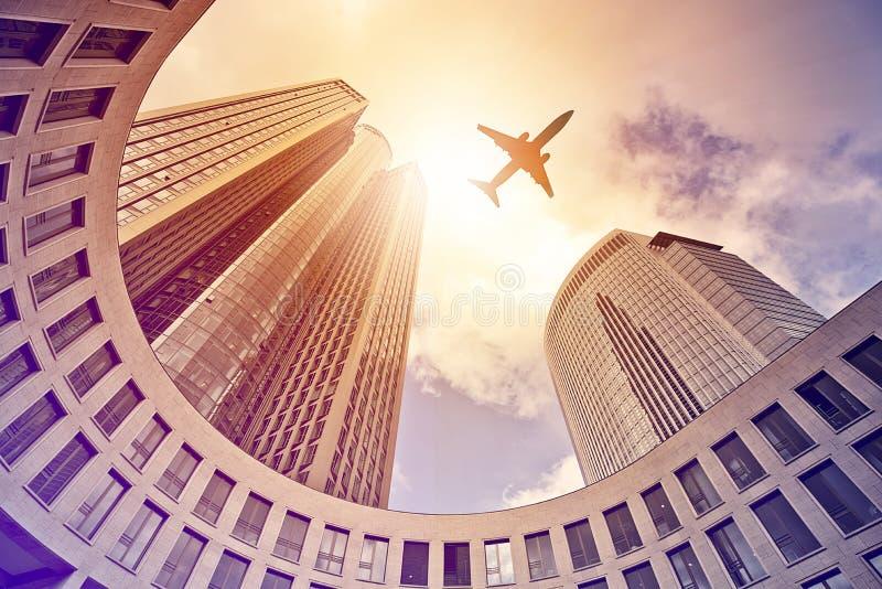 Αεροπλάνο που πετά πέρα από τους σύγχρονους πύργους γραφείων στοκ φωτογραφία