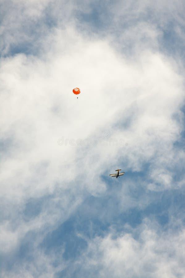 Αεροσκάφη και αλεξίπτωτο σε ένα υπόβαθρο των σύννεφων στοκ εικόνες