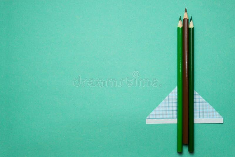 Αεροσκάφη φιαγμένα από μολύβια και έγγραφο για ένα πράσινο υπόβαθρο r στοκ φωτογραφία