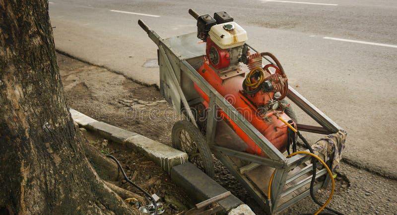 Αεροσυμπιεστής σε ένα κάρρο που χρησιμοποιείται συνήθως για να επιδιορθώσει μια φωτογραφία ροδών που λαμβάνεται στο Σεμαράνγκ Ινδ στοκ εικόνες