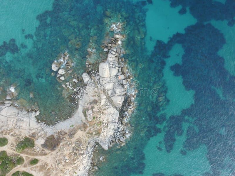 Αεροφωτογραφία της ακτής της Σαρδηνίας κατά τη διάρκεια ενός θερινού ηλιοβασιλέματος Μικρά κύματα στους βράχους που λαμβάνονται μ στοκ φωτογραφία