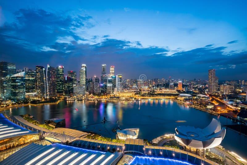 Αεροφωτογραφία της επιχειρηματικής περιφέρειας της Σιγκαπούρης στον ουρανό με τουριστικά αξιοθέατα τη νύχτα στο Marina Bay της Σι στοκ εικόνες