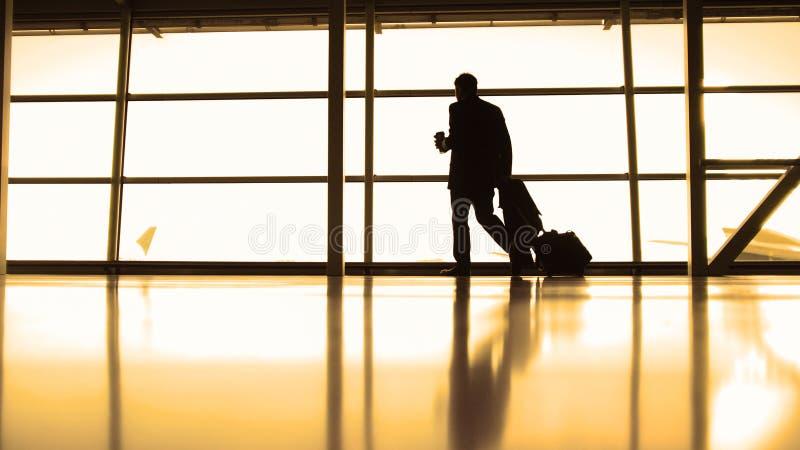 Αερολιμένας - διοικητής αεροσκαφών με τον καφέ για να πάει μπροστά από το παράθυρο, σκιαγραφία-θερμό στοκ εικόνες