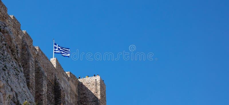 Αθήνα, Ελλάδα, βράχος ακρόπολη, ελληνική σημαία που κυματίζει στο σαφή μπλε ουρανό, έμβλημα στοκ φωτογραφία