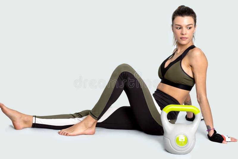 Αθλήτρια κατά τη διάρκεια ενός σπασίματος μετά από το workout με το kettlebell εικόνα στοκ εικόνα με δικαίωμα ελεύθερης χρήσης