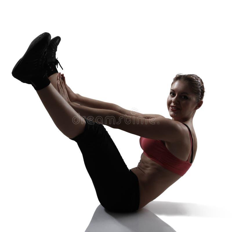 Αθλήτρια που κάνει την άσκηση ABS και ποδιών, πυροβολισμός στούντιο σκιαγραφιών στοκ φωτογραφία