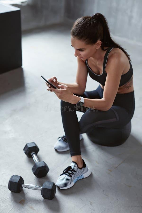 Αθλήτρια Sportswear μόδας που χρησιμοποιεί το τηλέφωνο στην κατάρτιση στοκ φωτογραφία με δικαίωμα ελεύθερης χρήσης