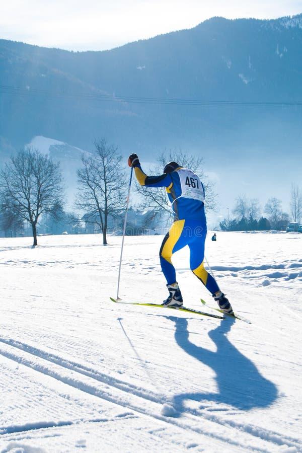 Αθλητής κατά τη διάρκεια ενός ερασιτεχνικού διαγώνιου αγώνα σκι χωρών σε μια ηλιόλουστη ημέρα στοκ φωτογραφία