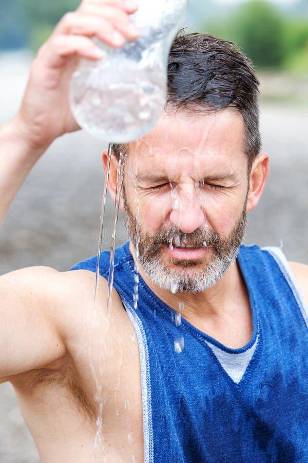 Αθλητής που στέκονται υπαίθρια και χύνοντας νερό σε τον στοκ φωτογραφία