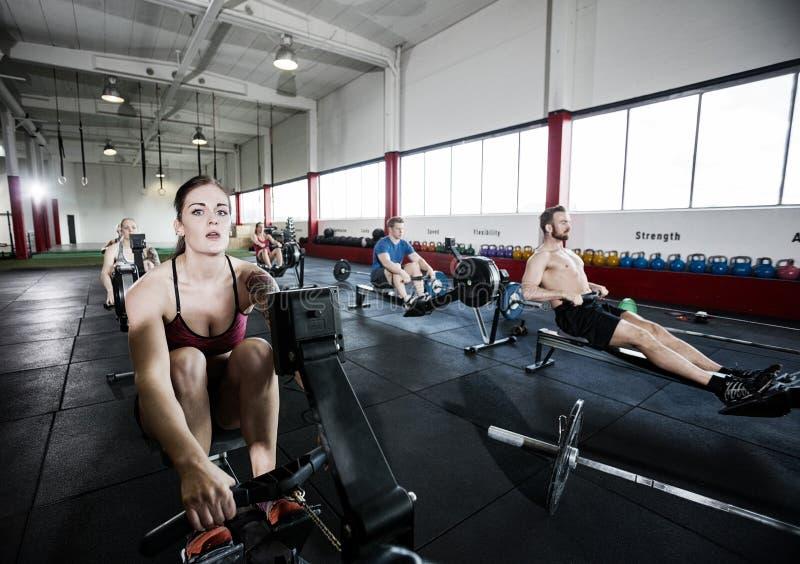 Αθλητής που χρησιμοποιεί τη μηχανή κωπηλασίας με τους φίλους στο κέντρο ικανότητας στοκ εικόνες