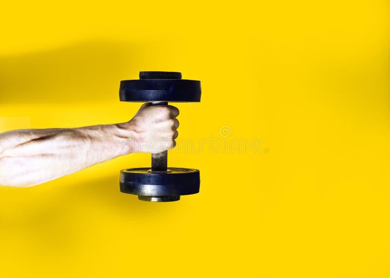 Αθλητής bodybuilder, κρατώντας υπό εξέταση έναν αλτήρα, μυϊκό χέρι σε ένα κίτρινο υπόβαθρο, το κείμενό σας εκεί, επίπεδος, αθλητι στοκ εικόνες