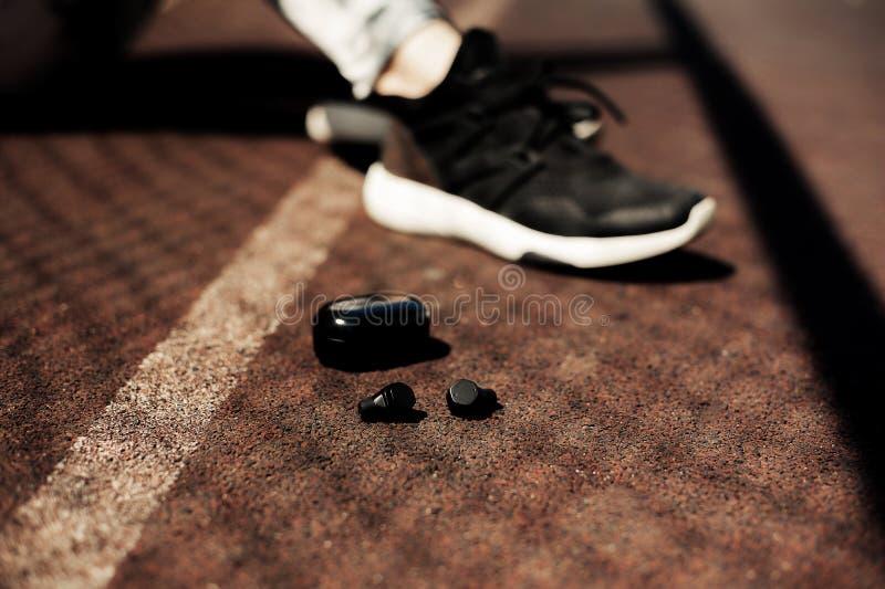 Αθλητικά φορετά εξαρτήματα νέας τεχνολογίας για τους δρομείς: αθλητικά ασύρματα ακουστικά ικανότητας, τρέχοντας παπούτσια Earbuds στοκ φωτογραφίες