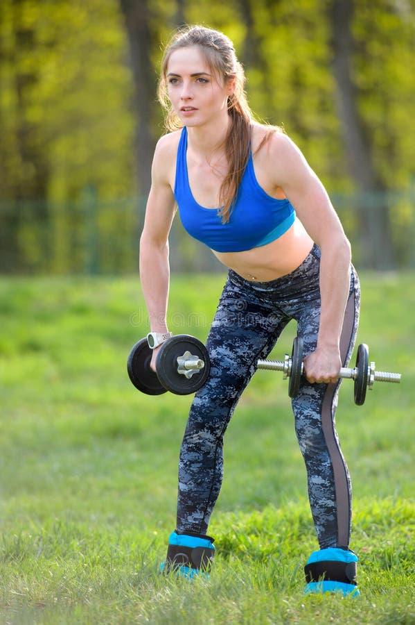 Αθλητική γυναίκα που κάνει την άσκηση για τα όπλα Φωτογραφία της μυϊκής πρότυπης επίλυσης ικανότητας με τους αλτήρες Δύναμη και κ στοκ φωτογραφία με δικαίωμα ελεύθερης χρήσης