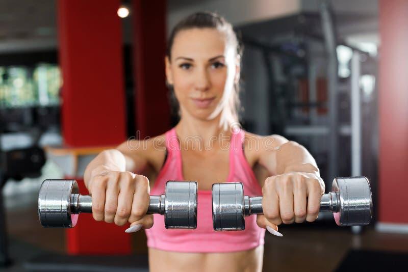 Αθλητική γυναίκα που κάνει την άσκηση με τους αλτήρες κοντά επάνω στοκ εικόνα
