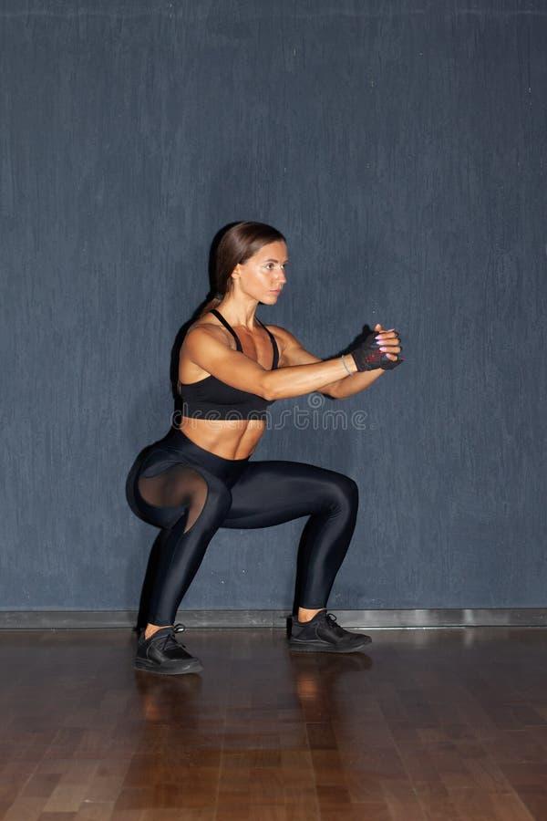 Αθλητική γυναίκα που κάνει τις στάσεις οκλαδόν στη γυμναστική στοκ εικόνες με δικαίωμα ελεύθερης χρήσης