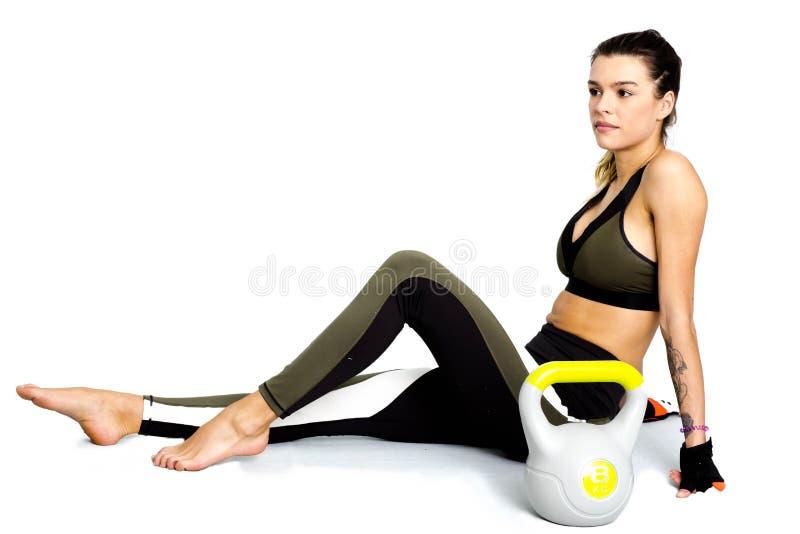 Αθλητική γυναίκα φωτογραφιών με το τέλειο σώμα που απομονώνεται στο άσπρο υπόβαθρο Δύναμη και συνεδρίαση motivati στο πάτωμα με τ στοκ φωτογραφίες