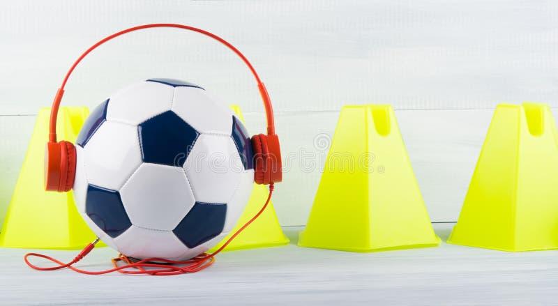 Αθλητική μουσική για τον αθλητισμό, σφαίρα ποδοσφαίρου με τα ακουστικά, στα πλαίσια των κίτρινων τριγώνων στοκ φωτογραφία