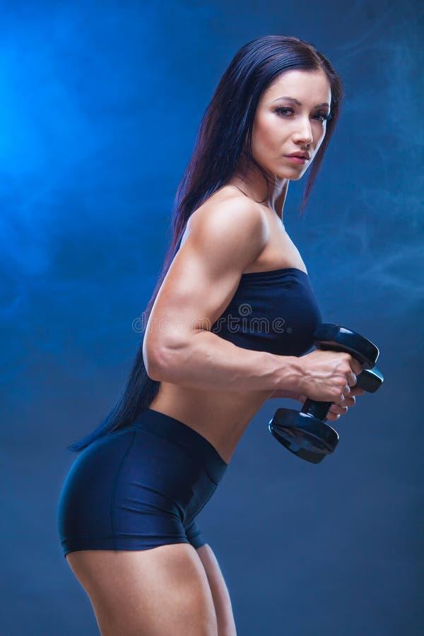 Αθλητική νέα γυναίκα που κάνει μια ικανότητα workout με τους αλτήρες στο μαύρο υπόβαθρο στούντιο Γύρω από τα σάβανα το πρότυπο στοκ φωτογραφία με δικαίωμα ελεύθερης χρήσης