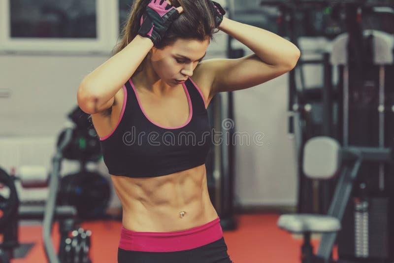 Αθλητική νέα γυναίκα που παρουσιάζει μυς μετά από το workout στη γυμναστική στοκ εικόνα με δικαίωμα ελεύθερης χρήσης