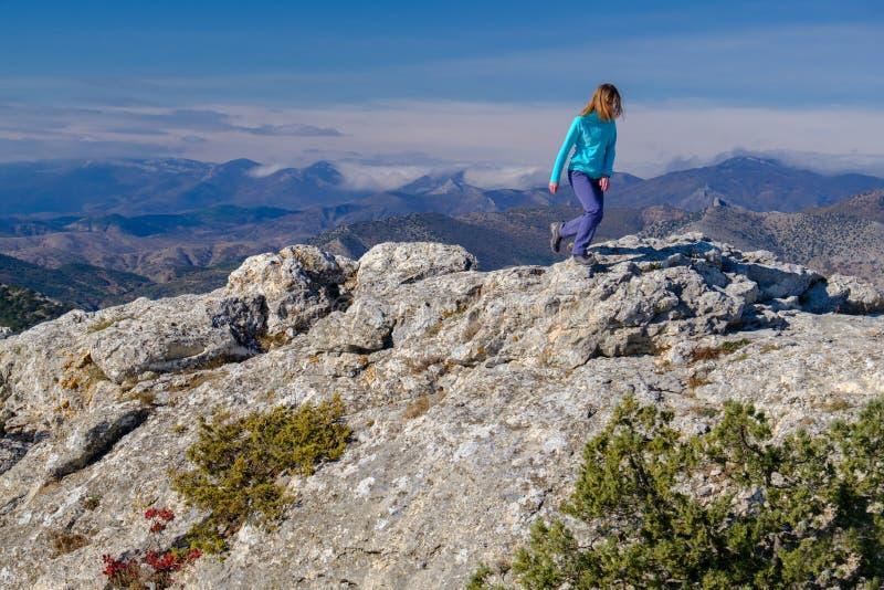 Αθλητική νέα γυναίκα που περπατά στη δύσκολη κορυφή του βουνού στοκ εικόνες